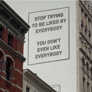 """Pretend billboard on the side of a building that says, """"Stop trying to be liked by everybody. You don't even like everybody."""""""
